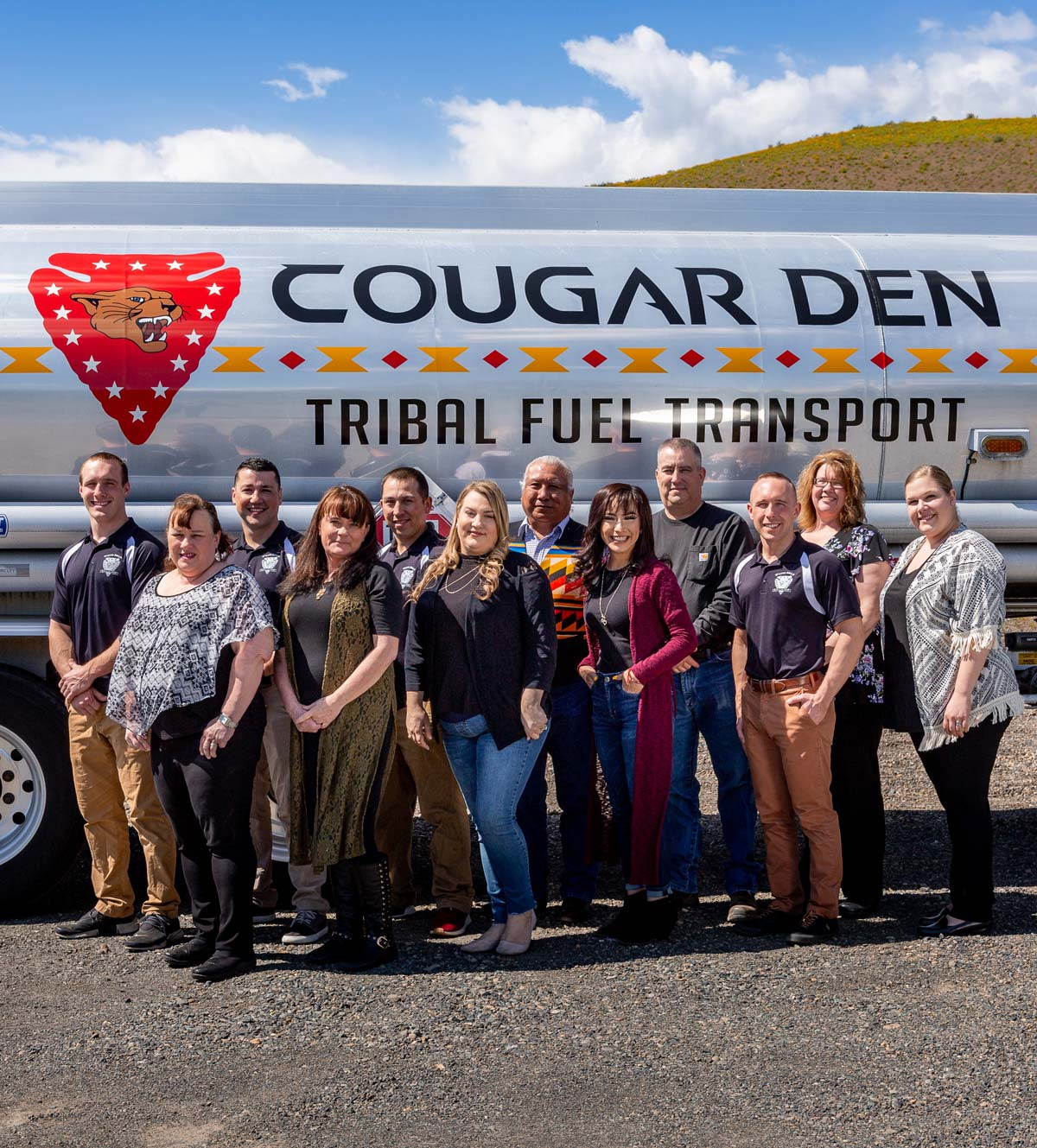 Cougar Den employees in front of Cougar Den fuel tank